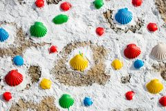 Colorful painted shells on white wall. Symbol of pilgrimage. Pilgrim sign on Camino de Santiago way. Street art. Outdoor decoration. Amount of sea shells royalty free stock photography