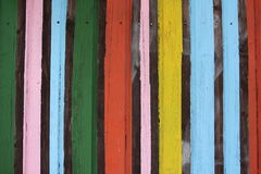 Colorful painted stripes on wooden wall. Close-up view of a wooden wall with colorful vertically painted stripes stock photo