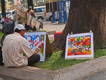 Colorful Painting. An artist at work under a shady tree Stock Photos