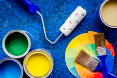 Colorful paints and brushes on blue wooden desk background top view Royalty Free Stock Image