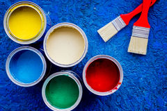 Colorful paints and brushes on blue wooden desk background top view Stock Photography