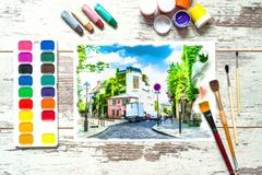 Colorful paints with brushes and a with an unfinished colorful drawing of a landscape on a piece of white paper. royalty free stock photography