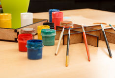 Colorful paints in cups and brushes ready for painting Stock Images