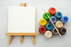 Colorful paints with paint brush and canvas on the easels. Colorful paints with paint brush and canvas on the easels, top view stock images