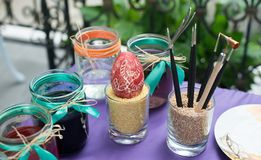 Colorful paints on palette with brushes ready for painting easter eggs Stock Photos