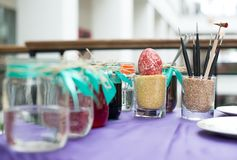 Colorful paints on palette with brushes ready for painting easter eggs Royalty Free Stock Photo