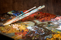 Colorful pallet. Painter's brushes and pallet full of colorful paint royalty free stock image
