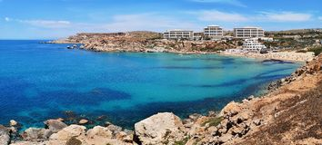 Colorful panorama with azure water and rocky seashore at Ghajn T Royalty Free Stock Photos