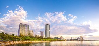 Panoramic view of city with cloudy sunset sky, sea and mountains on background. royalty free stock photography