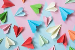 Colorful paper airplanes on pastel pink and blue colored background royalty free stock images
