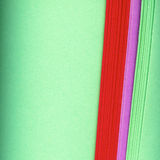 Colorful paper background. Abstract background of ends of different colored rolled paper on textured green with copy space Royalty Free Stock Image