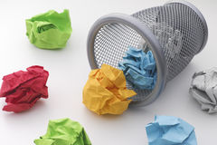 Colorful paper balls rolling out of trash can Stock Photos