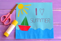 Colorful paper card with ship, sea, sun and words I love summer. Scissors and glue stick on lilac wooden background Stock Image