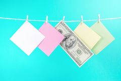 Colorful paper cards and money hanging rope isolated on blue background. royalty free stock photo