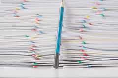 Colorful paper clip with pile of overload paperwork with pencil Stock Photo