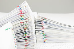 Colorful paper clip with pile of report place on finance account. Have blur pile of paperwork as foreground and background Royalty Free Stock Images