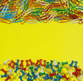 Colorful paper clip and pin isolated on yellow background Royalty Free Stock Photo