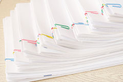 Colorful paper clip with step stack of overload paper. And reports place on wooden table Royalty Free Stock Photography