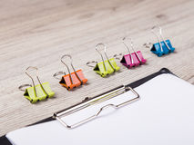 Colorful paper clip on wood background Stock Photos