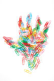Colorful paper clips arranged in hand shape Royalty Free Stock Photography