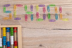Colorful paper clips arranged in an inscription - school. Wooden top of the school desk. Counters for counting