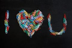 Colorful paper clips forming an alphabets and heart shape. Portrait of colorful paper clips forming an alphabets and heart shape on black wooden background Stock Image