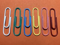 Colorful consecutive paper clips on orange background stock photo