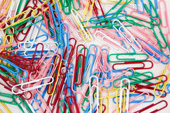 Colorful paper clips on a white background. Many Red, white, blue, pink and green paperclips on a white background Royalty Free Stock Image