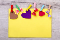 Colorful paper with clothespins. Fabric hearts and spotted bows. Mockup of congratulation on holiday. How to decorate greeting cards royalty free stock images