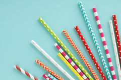 Colorful paper drinking straws on blue background. Stock Image