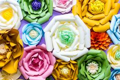 Colorful paper flowers on wall. Handmade artificial floral decoration. Spring abstract beautiful background and texture.  stock images