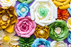 Colorful paper flowers on wall. Handmade artificial floral decoration. Spring abstract beautiful background and texture stock photography