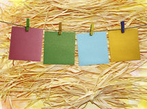 Colorful paper frame with clothespins on a straw Stock Photography