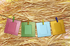 Colorful paper frame with clothespins on a straw Royalty Free Stock Image