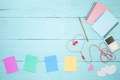 Colorful paper note with pencil and music player, red earphone o Royalty Free Stock Photo