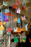 Colorful paper origami birds tied to strings Stock Image