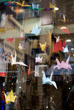 Colorful paper origami birds tied to strings. Hanging in air Stock Images