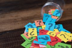 Colorful paper with question mark in a plastic jar on wooden table. Questions and diversity concept. FAQ and Q&A background concept stock photography