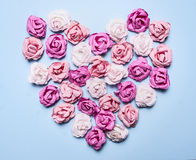Colorful paper roses laid out in a heart shape on a blue background decorations Valentine's Day top view close up Royalty Free Stock Photography