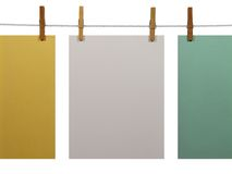 Colorful paper sheets on a clothes line (+clipping path). White, green and yellow blank paper sheets on a clothes line, isolated on white background. With stock images