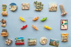 Various souvenir magnets and paper ships arranged on the blue background. Colorful paper ships and various souvenir magnets from several world country arranged stock photo