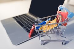 Colorful paper shopping bag in trolley on laptop. Customer can buy everything from office or home. Shopping online concept, Colorful paper shopping bag in stock image