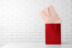 Colorful paper shopping bags on table against brick wall. Space for text stock image