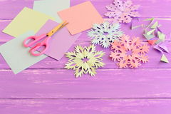 Colorful paper snowflakes, colored paper sheets and scrap, scissors on lilac wooden background Royalty Free Stock Images