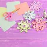 Colorful paper snowflakes ornaments, colored paper sheets and scrap, scissors on lilac wooden background. royalty free stock images