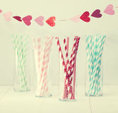 Colorful paper straws with a garland of hearts Royalty Free Stock Photos