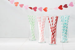 Colorful paper straws with a garland of hearts Stock Image