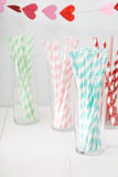 Colorful paper straws with a garland of hearts Royalty Free Stock Photography