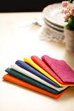 Colorful paper table napkins, flowers and plates Stock Images