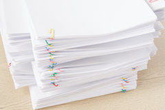 Colorful paperclip with pile of overload white document and reports. On wood table Stock Image